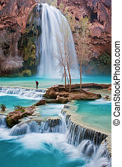 Young woman crossing a river at beautiful Havasu Falls . Havasupai Reservation - Havasu Canyon, Arizona.
