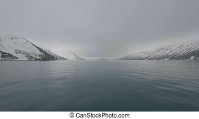 Landscape snowy mountain and smooth water surface of pacific...