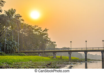 """Landscape view of a small village near river bank of """"Kumari"""", Mukutmanipur, Bankura, West Bengal. A beautiful landscape of rural India at sunset with clear sky and reflection on river water"""