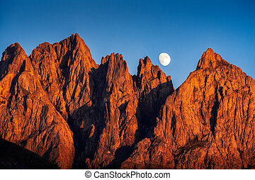 Landscape view of colorful mountain peaks at sunset with rising moon