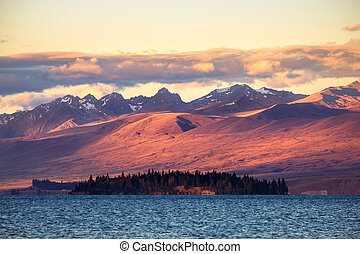 Landscape view of Lake Tekapo and mountains at sunset