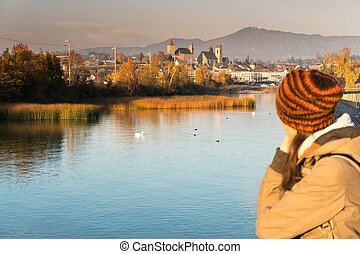 landscape view of marsh and lake shore with the town of Rapperswil in evening light and a young woman unfocused in the foreground