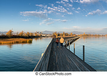 landscape view of marsh and lake shore with the town of Rapperswil in evening light and along wooden boardwalk in the foreground and a couple going for a leisurely walk