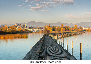 landscape view of marsh and lake shore with the town of Rapperswil in evening light and along wooden boardwalk in the foreground