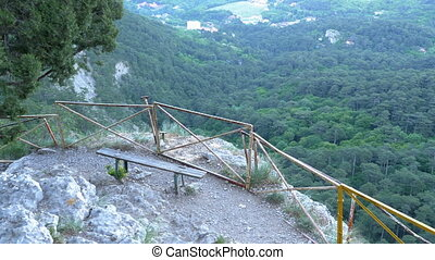 Landscape view of the mountain path and a bench on a cliff