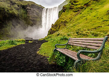 Landscape view of wild Skogafoss waterfall and bench, Iceland