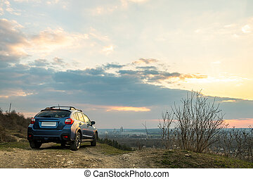 Landscape with blue off road car at sunset, Traveling by auto, adventure in wildlife, expedition or extreme travel on a SUV automobile. Offroad 4x4 vehicle in field at sunrise.