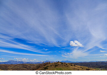 Landscape with blue sky and feather clouds