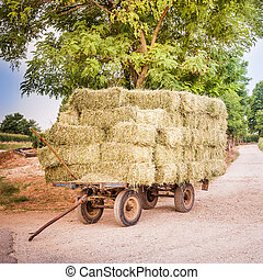 Farm cart with hay bales stacked left on the road