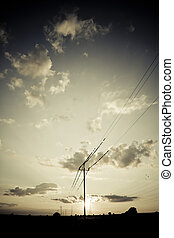 landscape with high tension wires over sky