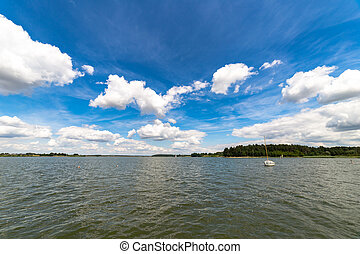 Landscape with lake in summer. Blue sky