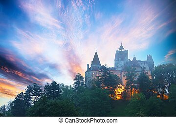 Landscape with medieval Bran castle known for the myth of Dracula at sunset