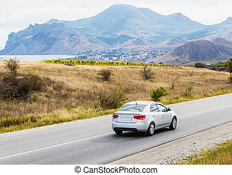 landscape with mountains, lake, road and car