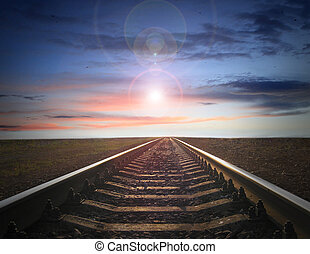 landscape with rails going away to evening sky with sun