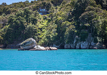 Landscape with Split Apple Rock or Tokangawha at Kaiteriteri beach, Abel Tasman National Park, New Zealand, South Island in bright summer sunshine, side view