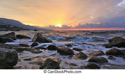 Landscape with the sunrise and sea waves breaking about stones