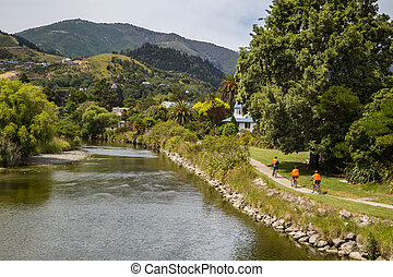 Landscape with three recreational cyclists in orange clothes alongside the river in Nelson, New Zealand