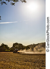 landscape with tractor plowing a field
