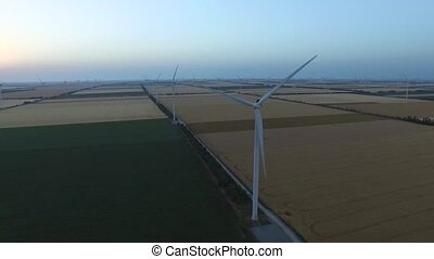 Landscape with windmills and farm fields at dusk. Aerial survey