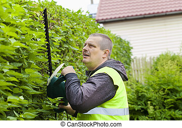 Landscape worker with an electric bush cutter