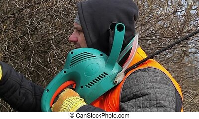 Landscape worker with bush cutter near bush