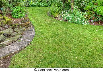 Landscaped garden scene with stone edging - A garden scene...