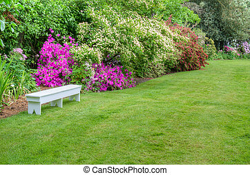 Landscaped garden scene with white bench