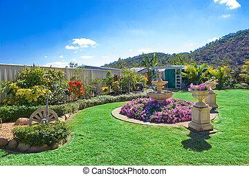 Landscaped gardens in backyard with beautiful waterfall