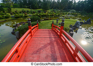 Landscaped grounds and traditional red bridge at the Japanese Garden in Singapore