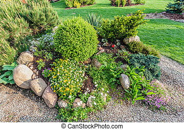 Landscaped summer garden with green plants, rocks, flowers in flowerbeds, mown grass.