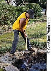 landscaper digging a pond.
