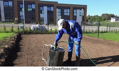 Landscaper man filling soil earth roller with water from ...