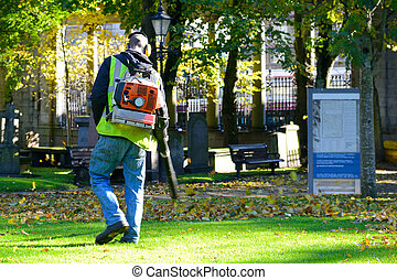 Landscaper operating petrol Leaf Blower in the city park.