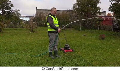Landscaping worker watering lawn