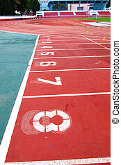 Lanes of a red race track with numbers and red seats in the stadium