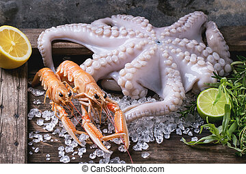 Raw octopus and langoustines on ice, served with herbs and lime over wooden table