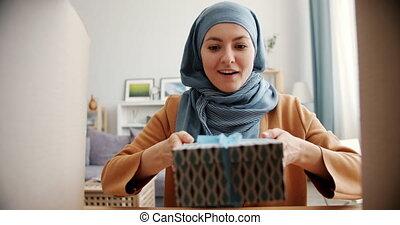 langsam, geschenk, nehmen, bewegung, lächeln, dame, gemischter, glücklich, rennen, öffnung, kasten, hijab