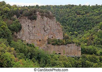 Lanscape with cave carved in the tuff rock near Sorano, Maremma, Tuscany, Italy