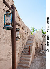 Lantern and ruins of the wall of Nizwa Fort, Oman