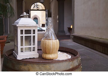 Lantern, bottle of wine and barrel in a street in the center of Lucca