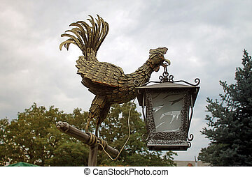 Lantern bronze cock statue in the park.