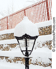 Lantern covered with snow on the background of a fence during a snowfall