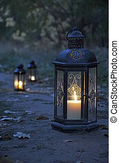 Lantern in darkness - Antique lanterns on an autumn path in...