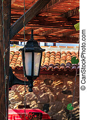 lantern in summer terrace shade - black lantern nailed to a...
