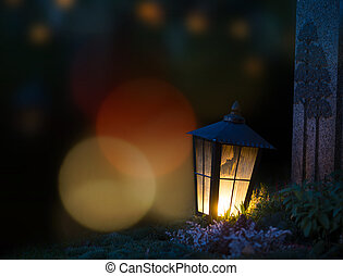 Lantern with lit candle on grave at night
