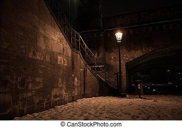 lantern standing close to a bridge on the river bank