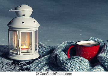 Lantern with a burning candle and a red mug with hot coffee on a snowy wooden table