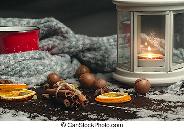 Lantern with a burning candle, spices and a red mug with hot coffee on a snowy wooden table