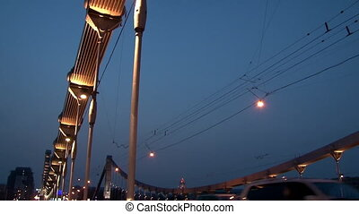 Lanterns on metal car hanging bridge over river in evening Moscow.
