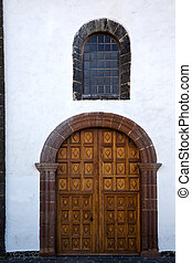 lanzarote spain canarias brass brown knocker in a closed wood church door and white wall abstract
